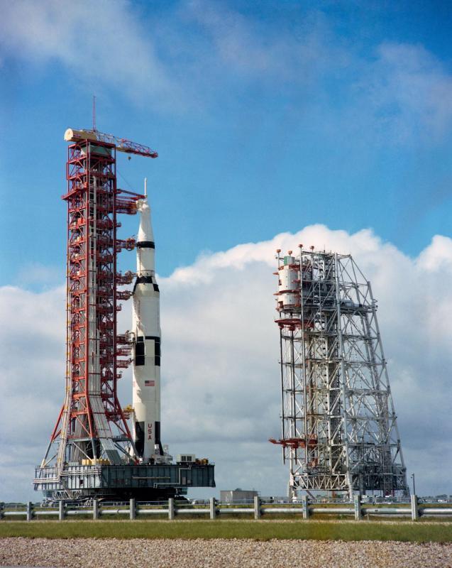 Crawler Transporter se svým nákladem - mobilní plošinou raketou Saturn 5 s lodí Apollo 12 - míří na vypouštěcí komplex 39A; vpravo je vidět služební věž