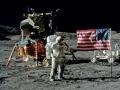 Gene Cernan zdraví vlajku na Měsíci; v pozadí rover a lunární modul Challenger