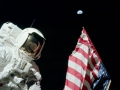 Je 11. prosince 1972 a posádka Apolla 17 uskutečňuje první výstup na měsíční povrch. Při té příležitosti kosmonauti instalují vlajku Spojených států. Na obrázku Jack Schmitt vyfotografovaný Genem Cernanem u vlajky, nad jejímž vrcholem se vznáší Země