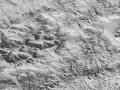 Tento obrázek ukazuje, jak eroze a poruchy vyřezaly část ledové kůry Pluta v této drsné, zničené zemi. Výrazný, 2 km vysoký útes, který na obrázku směřuje napříč z levého spodního rohu do pravého horního, je součástí velkého kaňonového systému, který se táhne stovky kilometrů přes severní polokouli Pluta. Členové týmu New Horizons se domnívají, že hory ve středu jsou tvořeny vodním ledem, ale byly přeměněny pohybem dusíku nebo jiných exotických ledů po delší období, takže mají zaoblené vrcholy a krátké hřebeny. V dolní části tohoto 80 km širokého obrázku se terén dramaticky přeměňuje do zlomu a jemně rozpukaného dna na severozápadním okraji obří ledové planiny neformálně pojmenované Sputnik Planum. V horní části obrázku je severozápad